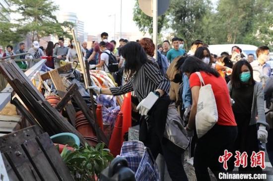 11月20日下午,有网民发起清理红磡海底隧道行动,大批香港市民响应召集,到红磡海底隧道九龙入口一带准备清理激进示威者破坏过后留下的垃圾和障碍物,但由于警方认为该处仍有潜藏危险性,不希望义工们冒险,义工们听从警方指示,但仍不断清理警方封锁线外围一带。图为香港市民将激进示威者用于堵路的障碍物搬离。中新社记者 谢光磊 摄