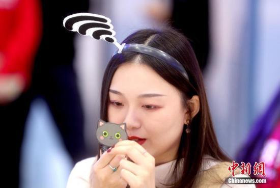 """11月21日,2019世界5G大会在北京举行,图为华为员工头戴""""信号头饰"""",准备制作小视频,向民众普及5G知识。/p中新社记者 张宇 摄"""