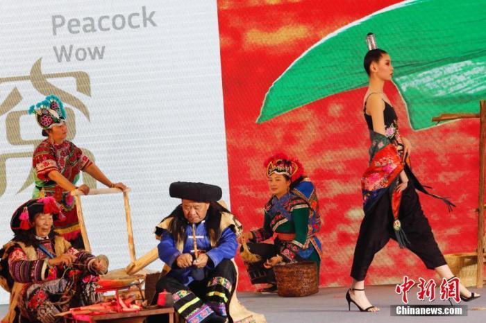 """11月21日,第二届长三角国际文化产业博览会在上海国家会展中心开幕。图为""""丝路云裳·七彩云南民族赛装文化节""""主题秀亮相会场,吸引了参观者的目光。主题秀分为原生态服饰部分和现代创新性民族服饰部分,通过全新的民族与时尚巧妙搭配的新颖感,为观众呈现一场把民族元素与时尚趋势完美搭配的民族服装秀。<a target='_blank' href='http://www.chinanews.com/'>中新社</a>记者 殷立勤 摄"""