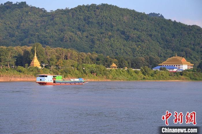 11月20日,湄公河上一艘货船从缅甸佛寺前经过。自2011年,中老缅泰四国启动了湄公河联合巡逻执法以来,湄公河金三角航道安全得到了保障,各国货船的数量和载重量不断增加。中新社记者 缪超 摄