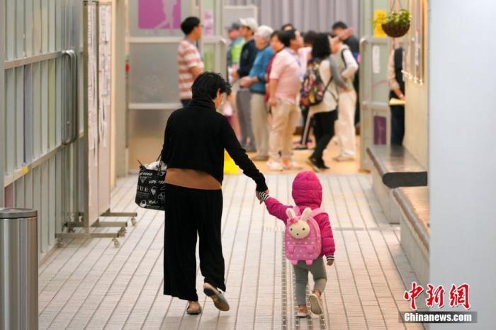 11月24日,香港特别行政区举行第六届区议会选举。图为选民一大早扶老携幼前往投票站投票。 <a target='_blank'  data-cke-saved-href='http://www.chinanews.com/' href='http://www.chinanews.com/'>中新社</a>记者 张炜 摄