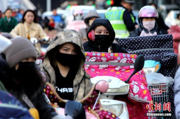 """11月25日,郑州遭遇降温天气,民众""""全副武装""""御寒出行。中新社记者 王中举 摄"""