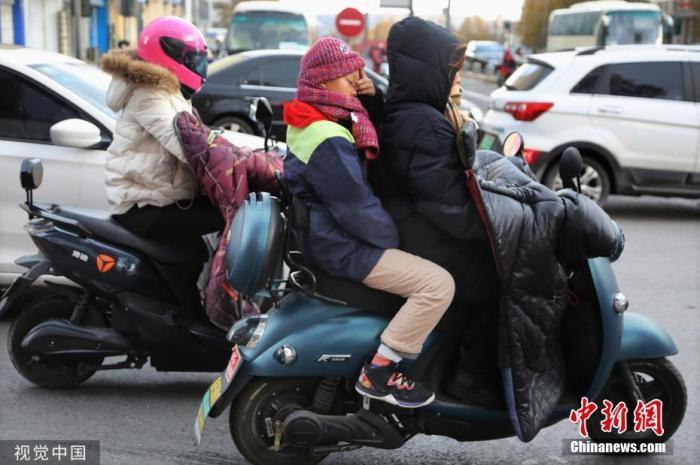 """资料图:天气寒冷,行人""""全副武装""""出行。王春 摄 图片来源:视觉中国"""