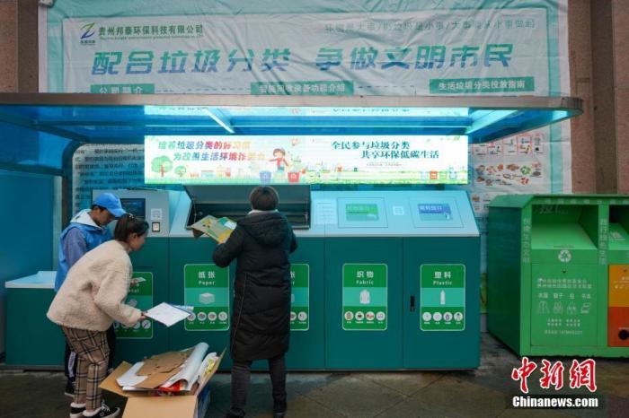 资料图片为:11月26日,在贵阳市花果园社区,两位贵阳市民在工作人员的帮助下进行垃圾分类投放。中新社记者 贺俊怡 摄