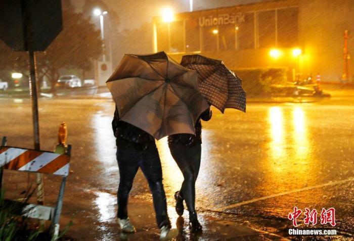 资料图:美国民众在狂风暴雨中前行。<a target='_blank' href='http://www.chinanews.com/'>中新社</a>记者 刘关关 摄