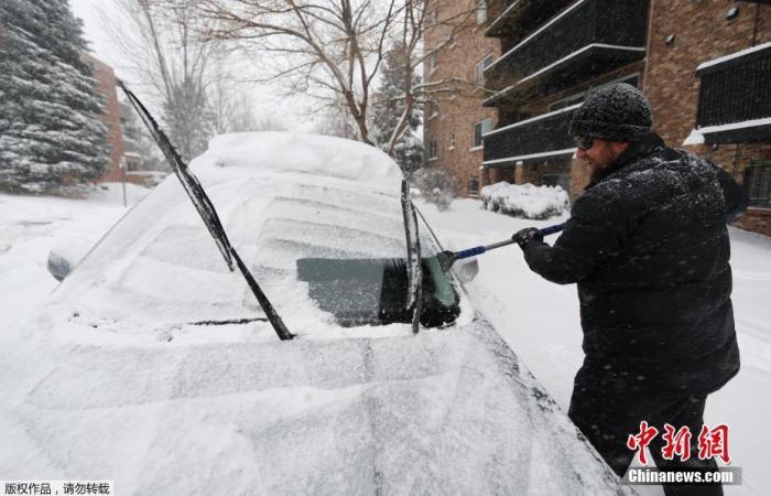 当地时间11月26日,美国丹佛市,一名男子在清理汽车上的积雪。