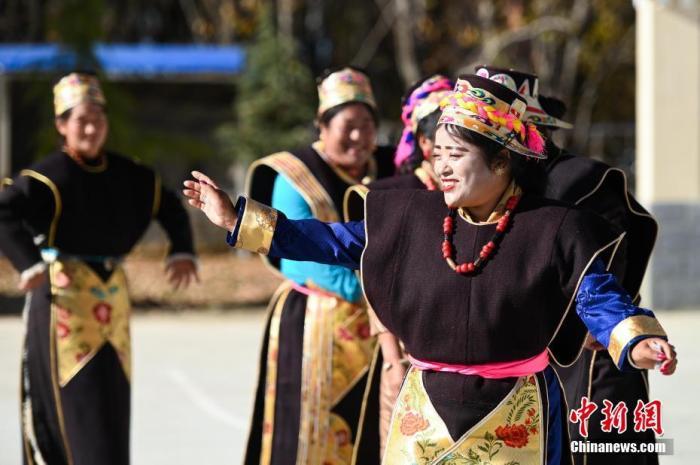 """11月27日,巴宜区米瑞乡通麦村民众身着节日盛装,载歌载舞,欢度工布新年。当日是藏历十月初一,西藏林芝迎来一年一度的工布新年。工布新年是工布地区(林芝市巴宜区、米林县、工布江达县一带)的地域性新年,是当地一年中最隆重的节日,也是西藏""""最早""""的新年。 中新社记者 何蓬磊 摄"""