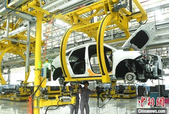 资料图为重庆一汽车生产车间内的工作人员正在组装车辆。 <a target=