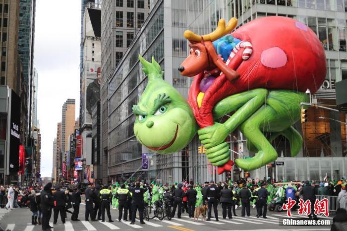 当地时间11月28日,第93届梅西感恩节大游走在纽约曼哈顿举走。图为动画电影《绿毛怪格林奇》中偷圣诞礼物的格林奇巨型气球走进在游走队伍中。中新社记者 廖攀 摄