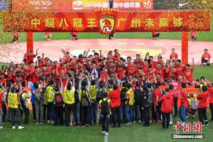"""12月1日,在刚刚结束的2019赛季中超末轮比赛中,广州恒大主场3:0战胜上海申花,队史第8次夺得中超冠军。广州恒大曾在2011至2017赛季完成中超7连冠伟业,本赛季又在与北京国安、上海上港的激烈竞争中成为赢家,从而荣膺中超""""八冠王""""。图为广州恒大淘宝队在夺冠庆典上庆祝。<a target='_blank' href='http://eudg.cn/'>中新社</a>记者 陈骥旻 摄"""