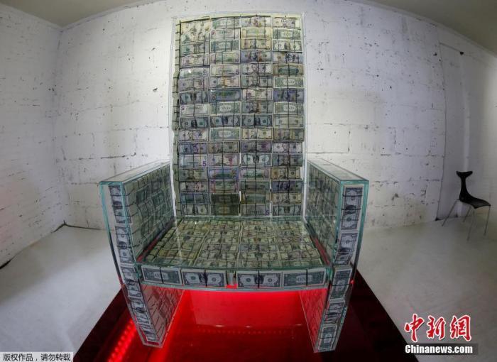 """当地时间11月29日,俄罗斯莫斯科,由俄罗斯艺术家Alexey Sergienko和企业家Igor Rybakov合作创作的艺术品""""金钱王座x10""""在当地展出,该装置是一个装有100万美元(约合703.08万元人民币)纸币的玻璃王座。"""
