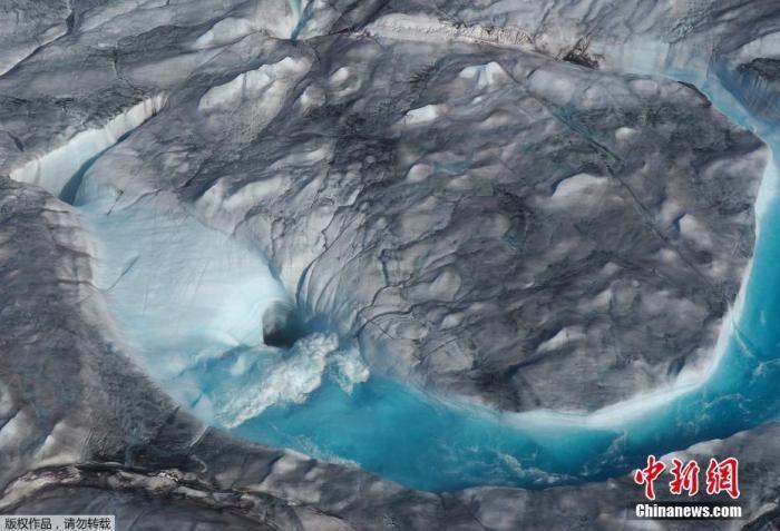 资料图:科学家使用无人机观察格陵兰冰原上一个湖泊的快速干涸和排水情况,这种现象由于气候变化而变得越来越普遍。图为格陵兰岛西部冰原上融冰的水形成的大河流入一个洞中。
