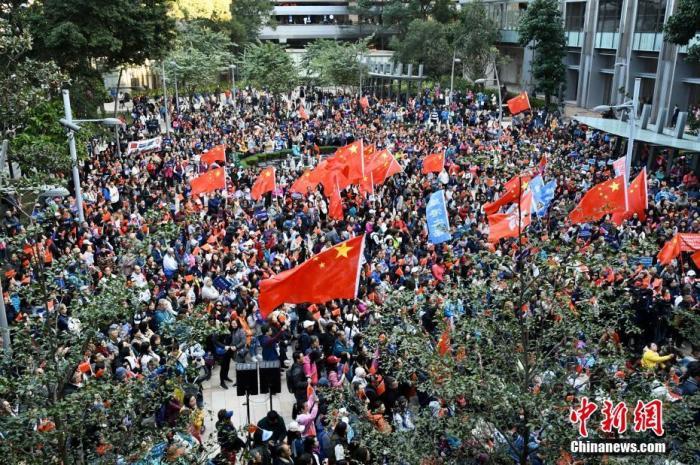 """12月7日下午,数千名香港市民在香港岛港湾道花园参与爱国护港撑警活动,他们手持国旗、标语,高唱国歌,表达反对暴力、维护法治、爱国爱港的心声。当日活动现场气氛热烈,有多位人士上台发言,呼吁广大市民支持警察严正执法,团结一心维护安宁等,收获现场阵阵掌声。在场市民高举国旗、区旗和标语,更不时高喊""""支持警察""""等口号。中新社</a>记者 李志华 摄"""