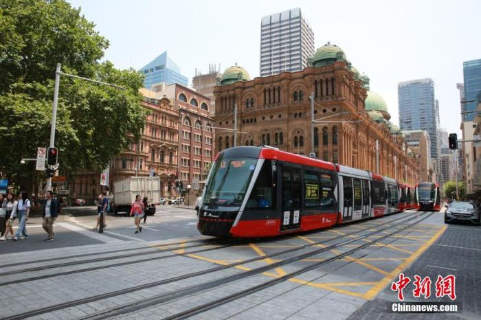 图为有轨电车通过悉尼地标性建筑维多利亚女王大厦。中新社记者 陶社兰 摄