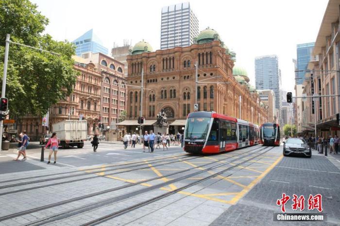 图为有轨电车通过悉尼地标性建筑维多利亚女王大厦。 中新社记者 陶社兰 摄