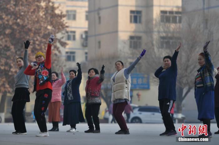 新疆喀什市东湖社区的小广场上,居民聚在一起跳广场舞。中新社记者 刘新 摄