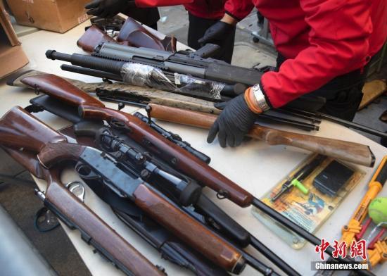 资料图:美国警方整理回收的枪支。中新社记者 刘关关 摄