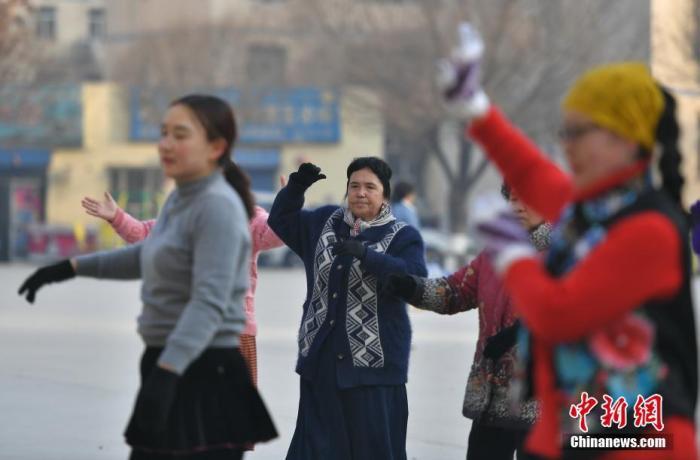 新疆喀什市东湖社区的小广场上,居民聚在一起跳广场舞。/p中新社记者 刘新 摄
