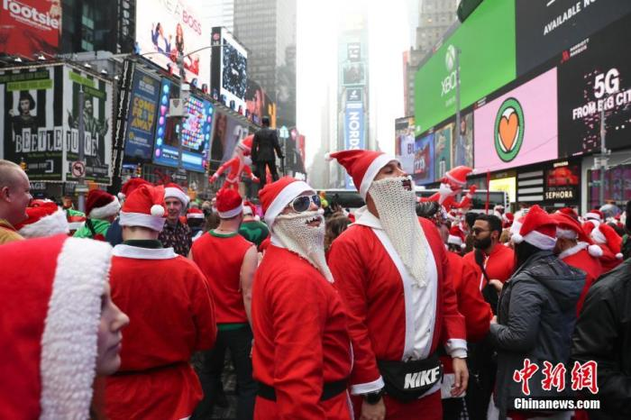 """当地时间12月14日,一年一度""""圣诞老人大游行""""在纽约举行,众多圣诞老人装扮的民众聚集在起始点时代广场。<a target='_blank' href='http://www.chinanews.com/'>中新社</a>记者 廖攀 摄"""