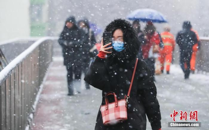 12月16日,北京迎来一场大雪,一名女子用手机拍摄雪景。北京市气象台15日发布了暴雪蓝色预警和道路结冰黄色预警信号。中新社记者 贾天勇 摄