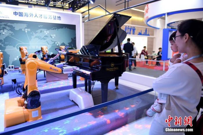 """12月18日,在""""海交会""""现场,智能装备""""机器人乐队""""正在演奏,吸引了民众的视线。 <a target='_blank' href='http://www.chinanews.com/'>中新社</a>记者 姬东 摄"""