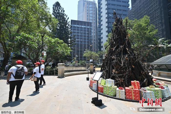 """当地时间12月18日,澳大利亚悉尼,当地街头竖起的""""烧焦的圣诞树""""装置。据悉,这座装置是为了支持澳大利亚红十字会的赈灾与恢复基金。目前,随着热浪和狂风的侵袭,澳大利亚林火持续,东海岸民众将面临新一轮威胁。"""