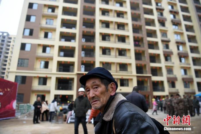 资料图:一名老人在安置房前驻足。<a target='_blank' href='http://www.chinanews.com/'>中新社</a>记者 康平 摄