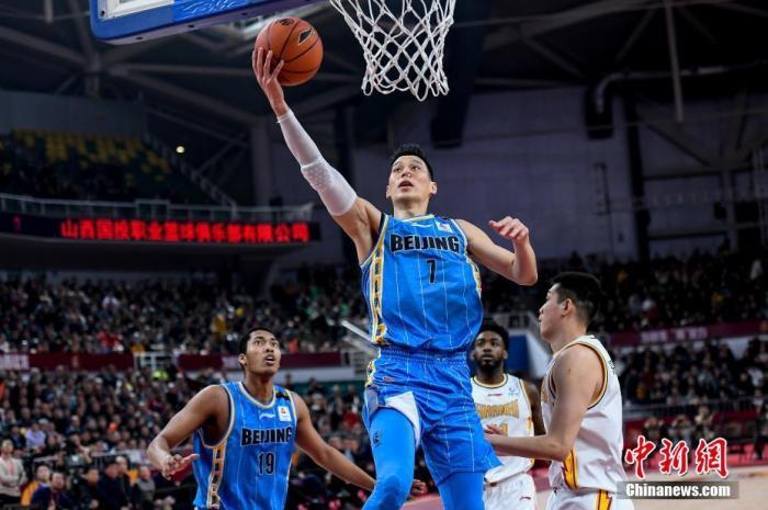 北京首钢球员林书豪(蓝)在比赛中持球上篮。 韦亮 摄