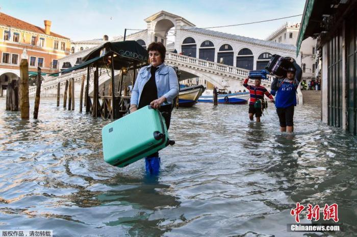 当地时间12月23日,意大利威尼斯的里亚托桥附近,一名女性拎着箱子涉水而行。