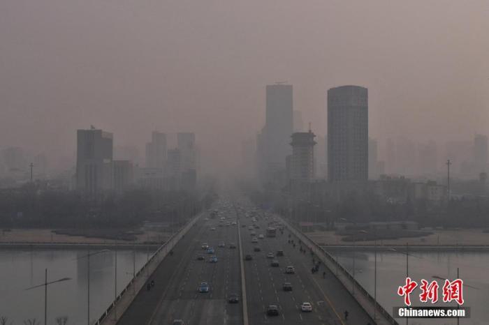 资料图:城市高楼在雾霾中若隐若现。中新社记者 武俊杰 摄