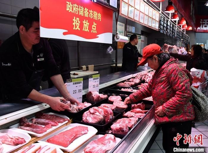 12月25日,重庆市市民在一家超市选购市政府投放的储备冻猪肉。据悉,为保障民众过好元旦和新春佳节,重庆市政府决定将11000吨储备冻猪肉在各超市进行为期40天的有序投放,增加市场供应。此次投放品种为Ⅱ号肉(前腿精瘦肉)和Ⅳ号肉(后腿精瘦肉),采取团体采购和市场零售两种方式,零售价格为每斤22元。中新社记者 周毅 摄