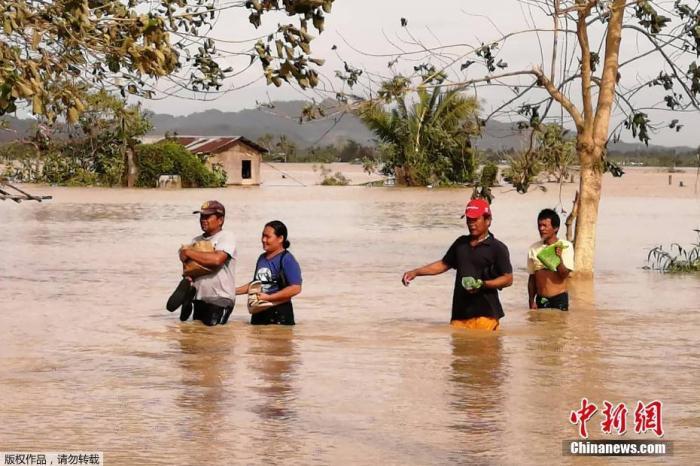 """当地时间12月26日,台风""""巴蓬""""席卷了菲律宾中部偏远村庄和受欢迎的旅游区。据报道,台风""""巴蓬""""圣诞节期间袭击菲律宾中部,造成房屋受损,村庄被淹,数万人在远离家园的疏散中心度过圣诞节。图为民众在洪水泛滥的公路上涉水前行。"""