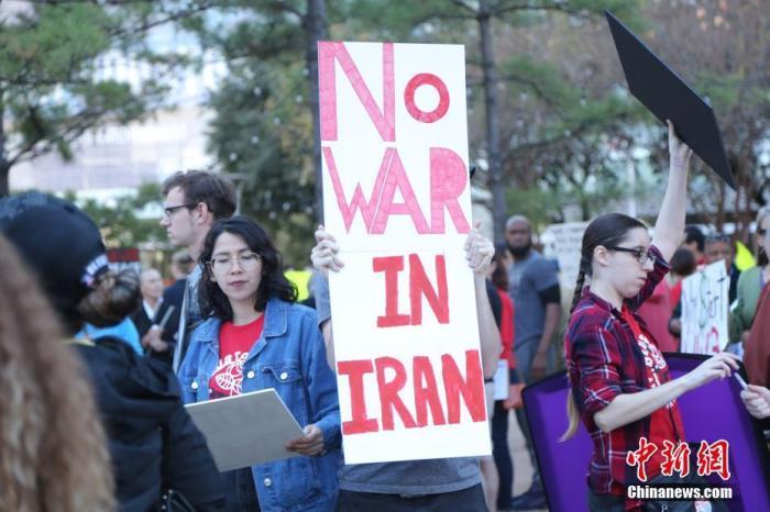 """当地时间1月5日,美国石油重镇休斯敦的民众举行反战集会,民众手持""""不对伊朗发起战争""""的标语。 <a target='_blank' href='http://www.zgzps.com/'>中新社</a>记者 曾静宁 摄"""
