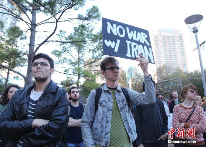 """当地时间1月5日,美国石油重镇休斯敦的民众举行反战集会,谴责美军炸死伊朗伊斯兰革命卫队下属""""圣城旅""""指挥官卡西姆·苏莱曼尼,反对美军向中东地区增派约3千名士兵的决定。图为集会民众手持""""不对伊朗发起战争""""的标语。 /p中新社记者 曾静宁 摄"""