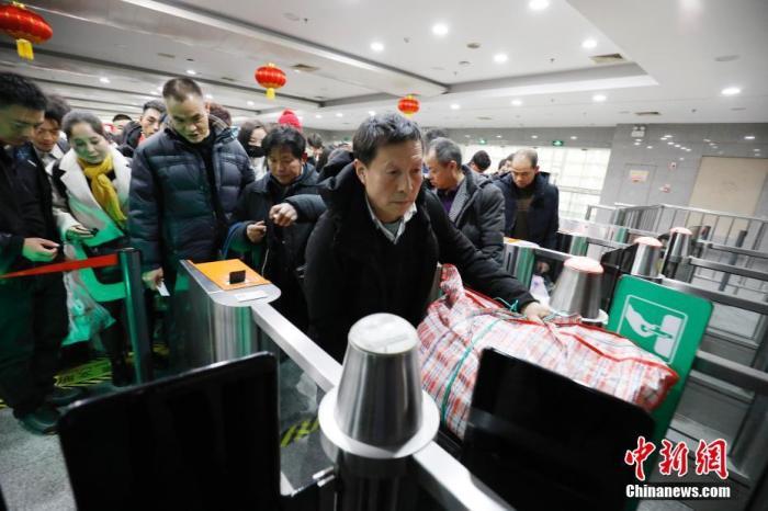 资料图:旅客在铁路上海站验票上车。殷立勤 摄