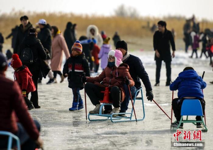 图为民众在博斯腾湖冰面上体验冰上运动项目。中新社记者 刘新 摄