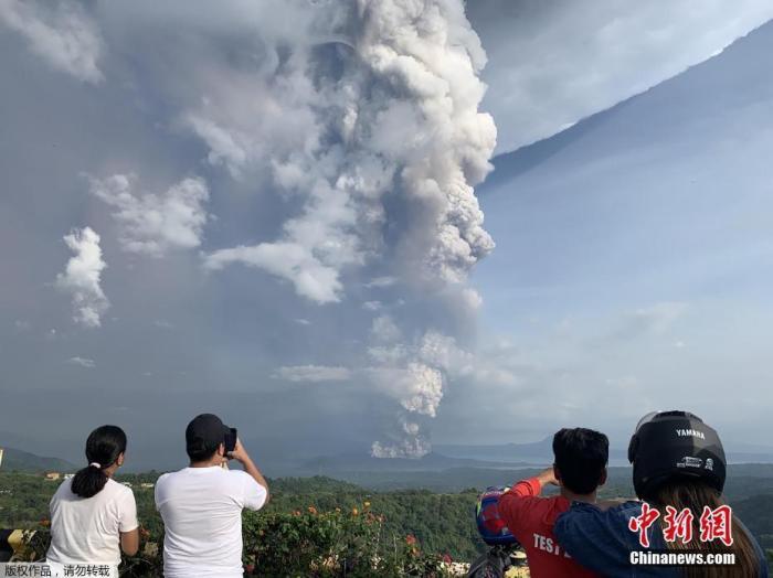 当地时间1月12日,菲律宾马尼拉西南卡维特省的塔盖泰镇,民众在给爆发的火山拍照。当地时间12日,菲律宾旅游胜地大雅台附近的塔尔火山开始喷发,火山灰高达10至15公里。