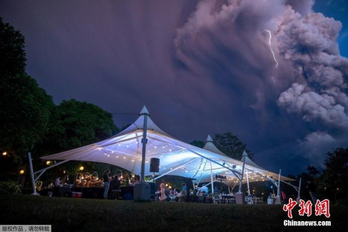 当地时间1月12日,菲律宾卡维特(Cavite)的阿方索,塔尔火山(Taal Volcano),开始剧烈活动,但一对新人仍然举行了婚礼。这对新人的身后,火山喷发出的大量浓烟伴随着闪电弥漫在空气中,场景震撼。