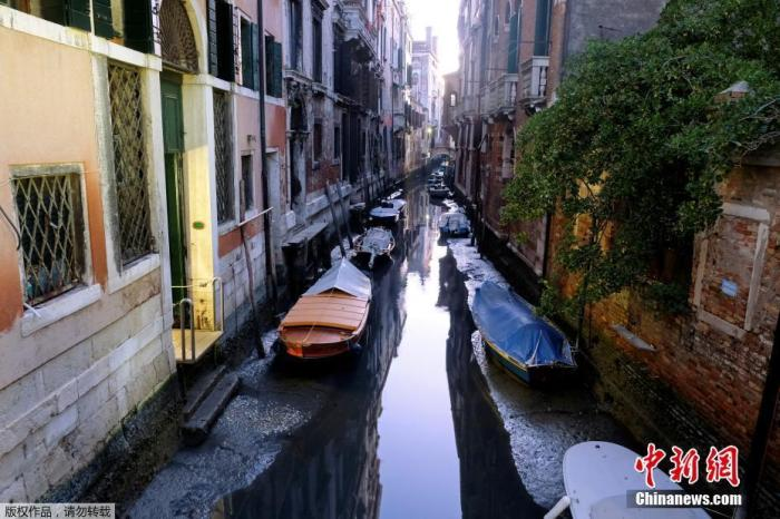 遭遇极端低潮的威尼斯水位大幅下降,河道上的船只几乎快搁浅。
