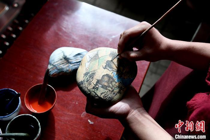 """图为1月13日,唐卡画师在一块石头上绘制以""""高原之舟""""牦牛为主题的唐卡。<a target='_blank' href='http://www.chinanews.com/'>中新社</a>记者 安源 摄"""