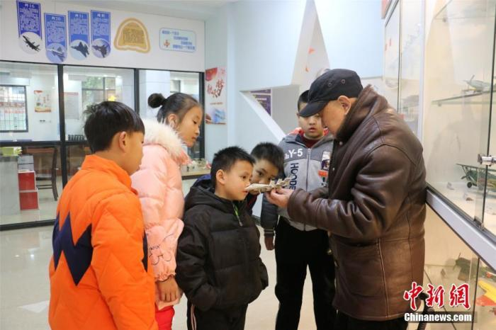 杨腾祥给孩子们展示其制作的飞机模型。 林馨 摄