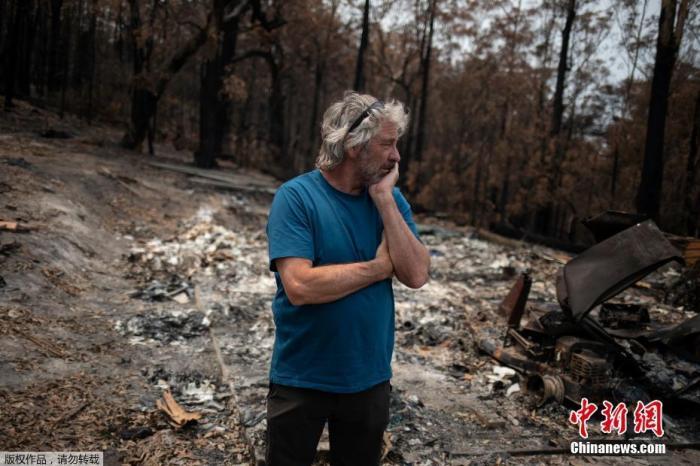 当地时间1月16日,澳大利亚冲浪者大卫·福特站在一片废墟旁满脸愁容。