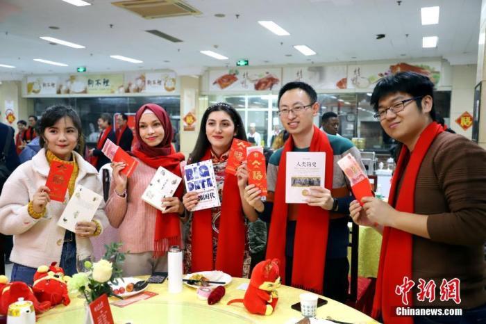 """1月17日,正值中国农历腊月二十三,俗称""""小年"""",天津大学校领导与留校学生欢聚一堂,听相声、吃饺子、发红包,给近200名中外师生送来新春祝福,共同迎接农历庚子年的到来。图为天津大学学生展示校领导发放的红包和书籍。 中新社记者 张道正 摄"""