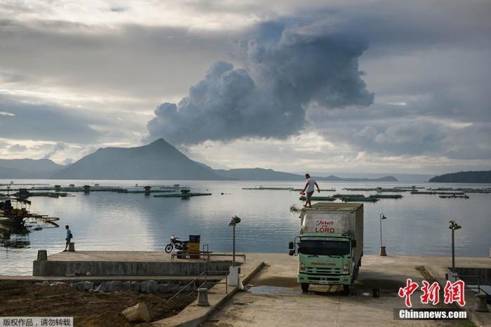 菲律宾首都马尼拉以南的塔阿尔火山于12日开始喷发,许多民众在能够远眺火山的观景处,与火山自拍留念。