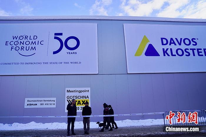 """当地时间1月19日,位于瑞士达沃斯的世界经济论坛年会(冬季达沃斯)会场准备就绪,与会者和媒体开始进行注册。主题为""""凝聚全球力量,实现可持续发展""""的第50届世界经济论坛年会将于1月20日至24日在达沃斯举行,预计将有来自全球117个国家近3000名政要、国际组织负责人、企业家和公民社会代表等嘉宾与会。图为主会场达沃斯会议中心门外纪念世界经济论坛创办50年的广告。中新社记者 彭大伟 摄"""