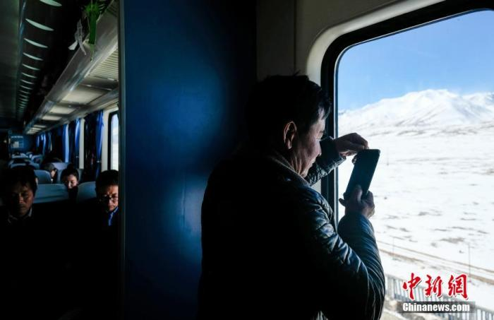 """临近中国农历新年的1月下旬一天,从拉萨开往上海的Z166次列车即将驶离有""""世界屋脊""""之称的西藏,前方是海拔5072米的唐古拉山口,世界铁路最高点。据旅客介绍,现在行驶在青藏铁路的列车都是弥散式供氧,车轮撞击铁轨的""""咣当""""声也没了,可以安心欣赏窗外的雪山、草原,走行青藏铁路真正成了一种享受。图为旅客在Z166次列车上拍摄窗外雪景。中新社记者 何蓬磊 摄"""