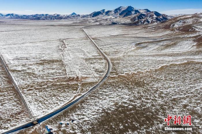 """临近中国农历新年的1月下旬一天,从拉萨开往上海的Z166次列车即将驶离有""""世界屋脊""""之称的西藏,前方是海拔5072米的唐古拉山口,世界铁路最高点。据旅客介绍,现在行驶在青藏铁路的列车都是弥散式供氧,车轮撞击铁轨的""""咣当""""声也没了,可以安心欣赏窗外的雪山、草原,走行青藏铁路真正成了一种享受。图为航拍青藏铁路那曲安多段。中新社记者 何蓬磊 摄"""
