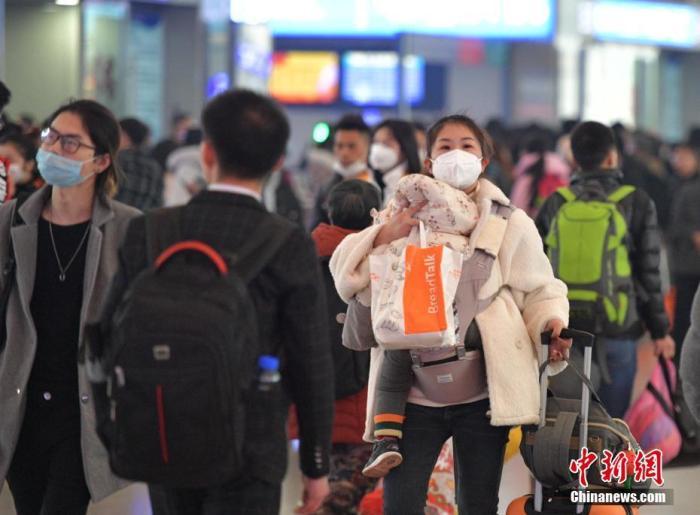 1月23日,成都火车东站迎来客流高峰,不少旅客佩戴口罩乘车。中新社记者 刘忠俊 摄