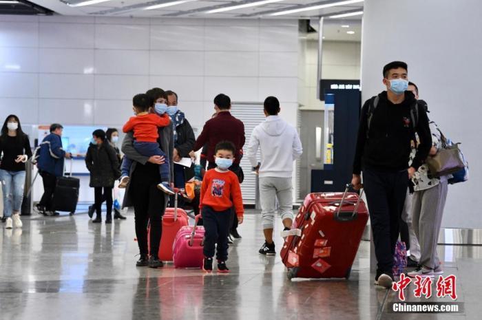 1月23日,排队市民、旅客均戴上口罩。香港铁路有限公司宣布,即时停售所有来往武汉的高铁车票。香港西九龙站大批市民排队、旅客办理改票/退票。中新社记者 李志华 摄