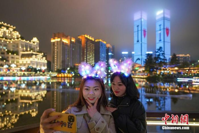 1月22日,两位女游客在双子塔前合影留念。当日,贵阳市花果园双子塔上演春节定制版灯光秀,吸引市民观赏。中新社发 贺俊怡 摄